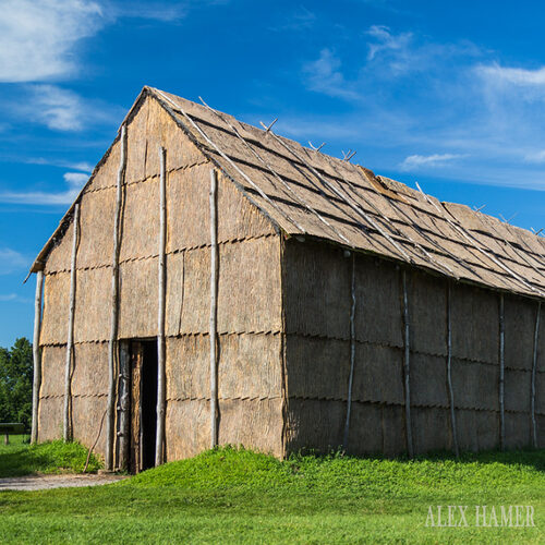 Eastern side of Seneca Bark Longhouse reproduction at Ganondagan with bright blue skies. Photo credit: Alex Hamer